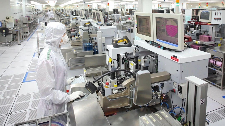 Un membro del team di produzione Micron indossa un cappello, abito e maschera speciale per aiutare a mantenere una stanza pulita e senza particelle