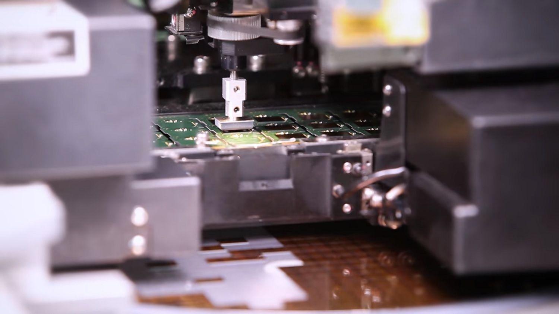 Una macchina prende un chip dall'alimentatore e lo posiziona sulla PCB