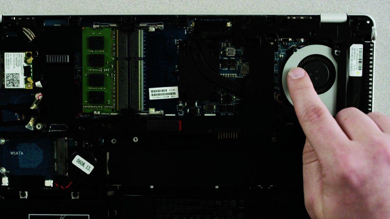 Una persona che tocca una superficie metallica non verniciata su un computer portatile per scaricare elettricità statica.