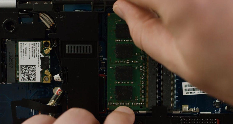 Una persona che stacca i moduli di memoria RAM dall'interno di un computer portatile