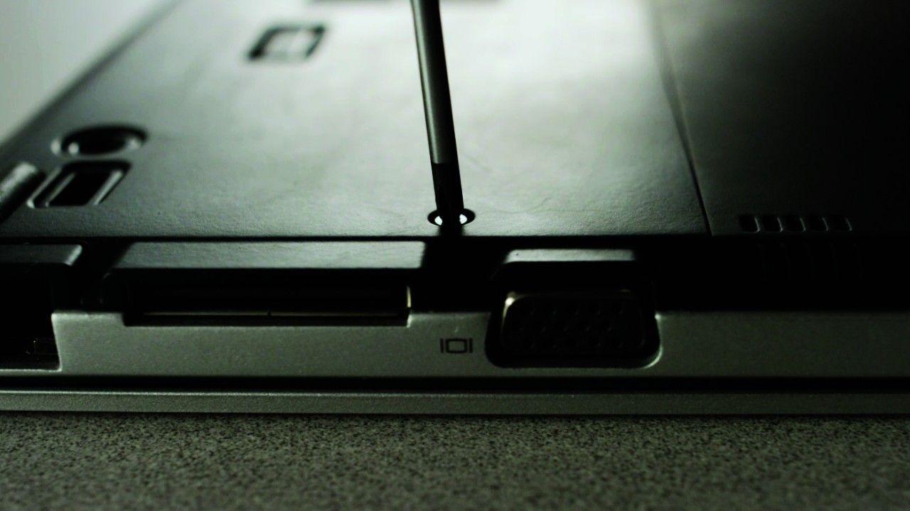 Un cacciavite che rimuove le viti dalla parte posteriore di un computer portatile
